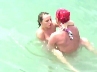 Sex on the beach. Two couples fuck in the water.