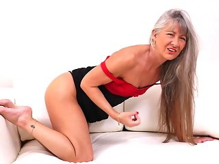 Mature blonde woman in red sandals with high heels likes to play with her pussy