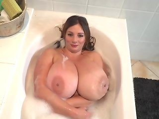 Busty babe, Nadine Jansen is playing with her massive milk jugs, in the bath tub